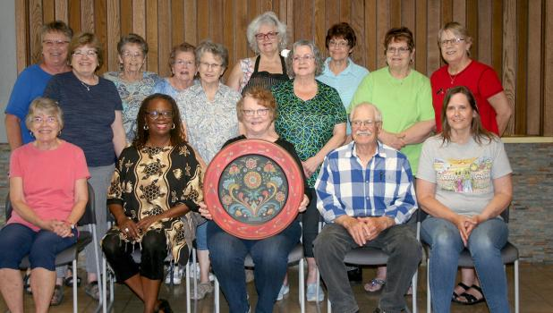Rosemalers who took the Os class are pictured here with teacher Trudy Peach who is holding her example of Os rosemaling. Seated in the front row from left to right: Sherry Yaeger, Debra Klepp, teacher Trudy Peach, Ray Sundquist, and Jean Christianson. In the back row from left to right: Marge Trembath, Lynn Sundrud, Connie Nelson, Ardella Lindberg, Barb Brooks, Becky Colebank, Jane Bellefy, Judy Merschman, Dawn Portz, and Sandy Sather.