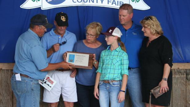 The Thorbeck-Imle family being presented with the Century Farm award at the Clearwater County Fair. The Imle family from left to right: Paul, Kathy, Sarah, Peter and Tracy.
