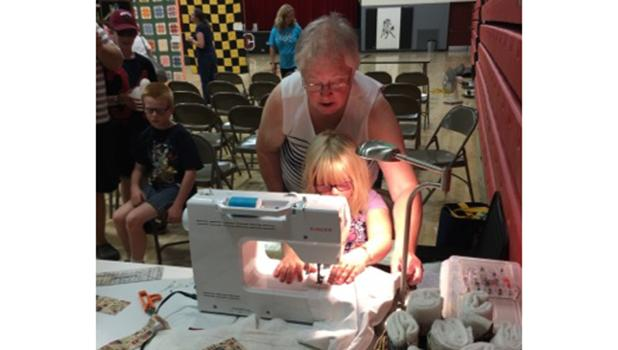 Shirley Dessellier helping Nicolina Hofstad with her Make n' Take project at Oklee Market Day on August 13th.