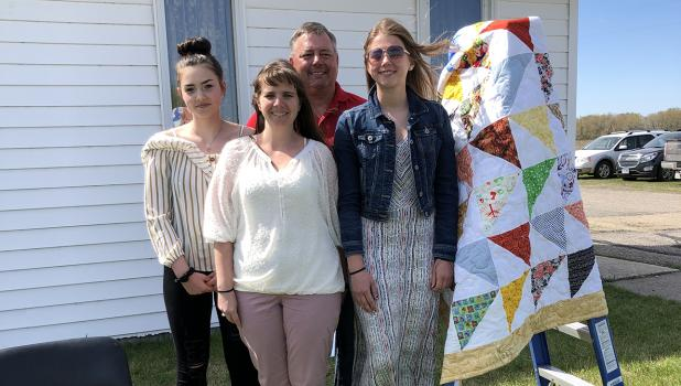 Sister Paige, parents Conway and Kim Olson stand with their graduate, Sidney Olson by the quilt she received from the Salem WELCA.