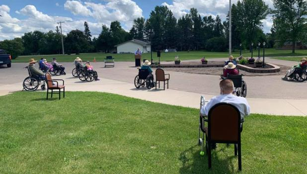 McIntosh Senior Living residents enjoyed music and entertainment by Pastor Karl Anderson outside of the residence on a bright, sunny day, while practicing their social distancing.