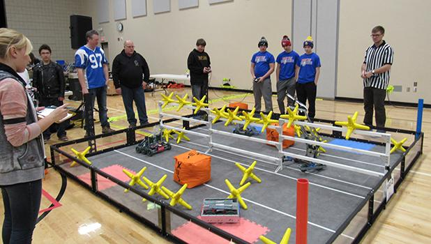 The playing field for the robotic competitions are set up in a school gym and with an announcer and a referee in a striped shirt, the competition has the aura of a sporting event. Here a Win-E-Mac School team is partipating in a competition.