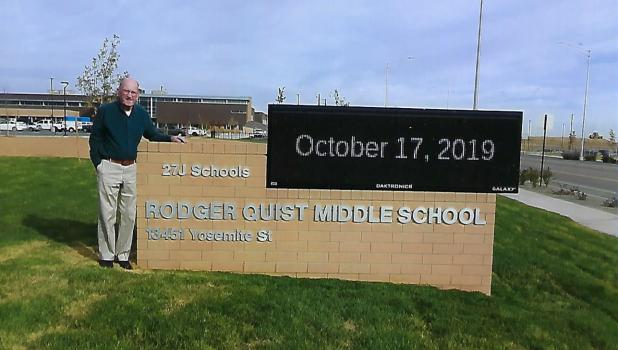Rodger Quist standing in front of the new sign of the new school named after him. Quist is a 1958 graduate of Oklee High School. Photo submitted