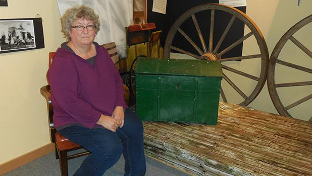 """Tamara Edevold is in her 26th year as the Historical Society Executive Director. This is an area of the """"1896 – The Home Place"""" display, which she and the museum staff designed and built, and is currently being featured at the History Museum in Shevlin. """"I love telling the stories of the people,"""" she says. """"The old stuff is awesome to have too, but it's about the people and learning about their history."""""""