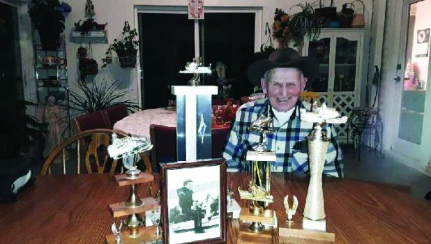 Bennie Erickson with some of his trophies and the picture that was in the Leader-Record in 1971.