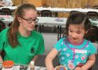 Sarah Quick, 4-H County Ambassador, is helping participant Alice Warne during the 4-H Make It and Take It Project Night.