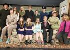 Seated (l to r): Abby Walton as Mr. Witherspoon, Sydney Melby as Abby Brewster, Hannah Kolstoe as Martha Brewster, Kara Longtin as Elaine Harper, Tom Nelson as Mortimer Brewster, Natalie Aakhus as Teddy Brewster, and Remy Ransack as Mr. Gibbs. Back row (l to r): Nick Pahlen as Jonathan Brewster, Jade Person as Dr. Einstein. Tera Qualley as Officer Brophy, Britain Arlt as Rev. Dr. Harper, Heather Longtin as Lieutenant Rooney, Jayden Iverson as Officer Klein, Dede Walton as Officer O'Hara.