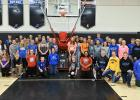 Boys and girls basketball players at RLCC standing by the new shooting machine which was made possible from donations by individuals and businesses.