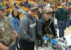 Four members of the RLCC robots team (Austin Erlandson, Angel Auman, Brandon Lee, and Dylan Gustafson) with their robot at the pre-final match check in and inspection.