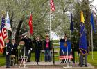 Program participants stand at attention as the national anthem is being played. Left to right: Barry Rewertz holding the American flag, Marv Engesether, Chaplain Les Hofstad, guest speaker Specialist Brandi Malwitz, Alice Jobe of the Plummer American Legion Auxiliary, Past Commander Clarence Gagner as program moderator, and others hidden by the Legion flag.