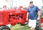 Dustin Neuschwander is pictured next to his restored Farmall H tractor. (See the article to the right.)