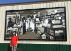 The mural was hung on the side of the Grygla Coop Store on August 19th. Beau Bakken stands next to his creation.